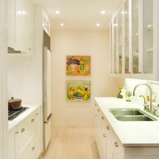 На фото: маленькая параллельная кухня в стиле современная классика с двойной раковиной, стеклянными фасадами, белыми фасадами, техникой под мебельный фасад, обеденным столом, столешницей из акрилового камня, белым фартуком, фартуком из керамической плитки, светлым паркетным полом и белым полом без острова с