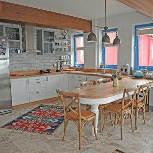Modelo de cocina comedor en U, costera, pequeña, con fregadero de un seno, armarios abiertos, puertas de armario blancas, encimera de zinc, suelo de travertino y una isla