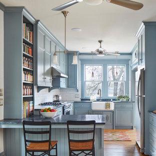 Diseño de cocina en U, de estilo americano, con fregadero sobremueble, armarios estilo shaker, puertas de armario azules, salpicadero blanco, salpicadero de azulejos tipo metro, electrodomésticos de acero inoxidable, suelo de madera clara, península y encimeras grises