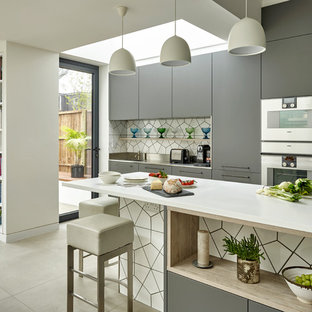Contemporary single-wall kitchen/diner in London with flat-panel cabinets, grey cabinets, composite countertops, white splashback, ceramic splashback, stainless steel appliances, ceramic flooring, an island and grey floors.