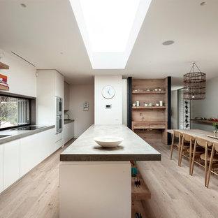 Modelo de cocina de galera, actual, con suelo de madera clara, fregadero bajoencimera, armarios con paneles lisos, puertas de armario blancas y península