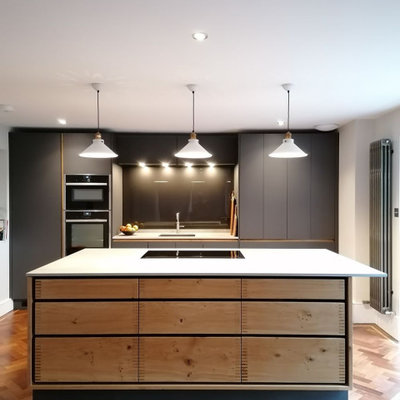 Example of a large trendy galley brown floor kitchen design in Hertfordshire with an undermount sink, flat-panel cabinets, gray cabinets, black backsplash, glass sheet backsplash, paneled appliances, an island and white countertops