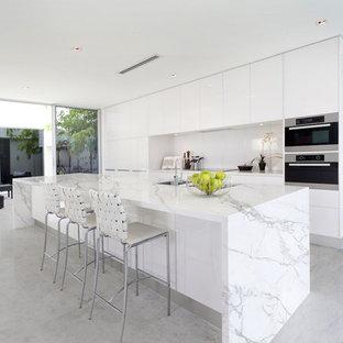 На фото: параллельная кухня в современном стиле с плоскими фасадами, белыми фасадами, белым фартуком, техникой из нержавеющей стали, островом и двойной раковиной с