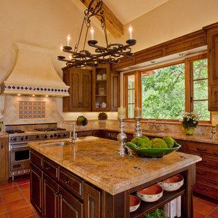 サンフランシスコの地中海スタイルのおしゃれなキッチン (御影石カウンター、レイズドパネル扉のキャビネット、中間色木目調キャビネット、ベージュキッチンパネル、シルバーの調理設備の) の写真
