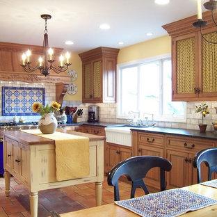 フィラデルフィアの中サイズのカントリー風おしゃれなキッチン (エプロンフロントシンク、レイズドパネル扉のキャビネット、中間色木目調キャビネット、ソープストーンカウンター、白いキッチンパネル、サブウェイタイルのキッチンパネル、パネルと同色の調理設備、セラミックタイルの床) の写真