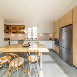Idéer för ett litet modernt orange kök, med vita skåp, laminatbänkskiva, vitt stänkskydd, stänkskydd i keramik, rostfria vitvaror, betonggolv, grått golv, en nedsänkt diskho och släta luckor