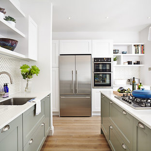 Classic kitchen in London with a submerged sink, shaker cabinets, green cabinets, multi-coloured splashback, stainless steel appliances, medium hardwood flooring, an island and beige floors.