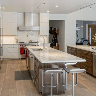 Inspiration for a transitional open plan kitchen in Denver with an undermount sink, flat-panel cabinets, white cabinets, granite benchtops, white splashback, ceramic splashback, stainless steel appliances, light hardwood floors, multiple islands and pink floor.