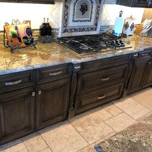 Esempio di una grande cucina stile rurale con lavello sottopiano, ante con bugna sagomata, ante marroni, paraspruzzi beige, paraspruzzi in travertino, elettrodomestici in acciaio inossidabile, pavimento in travertino, 2 o più isole, pavimento beige, top beige e top in granito