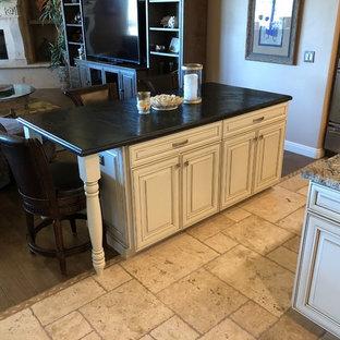 Idéer för ett stort rustikt beige linjärt kök med öppen planlösning, med en undermonterad diskho, luckor med upphöjd panel, bruna skåp, beige stänkskydd, stänkskydd i travertin, rostfria vitvaror, travertin golv, flera köksöar, beiget golv och granitbänkskiva