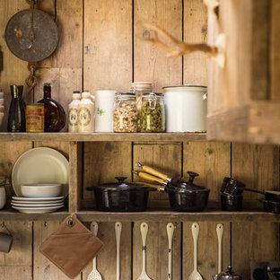 This is an example of a small country eat-in kitchen in Cornwall with a farmhouse sink, medium wood cabinets, panelled appliances, medium hardwood floors and concrete benchtops.