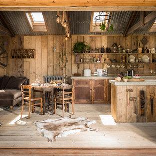 Diseño de cocina comedor de galera, rústica, pequeña, con fregadero sobremueble, armarios con rebordes decorativos, puertas de armario de madera oscura, electrodomésticos con paneles, suelo de madera clara y encimera de cemento