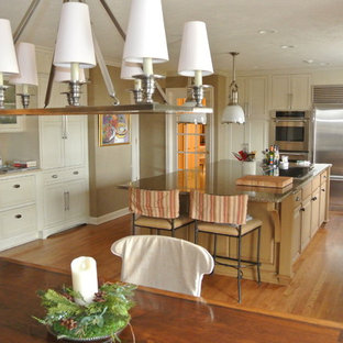 Photo of a large transitional l-shaped eat-in kitchen in Omaha with a double-bowl sink, beaded inset cabinets, brown cabinets, recycled glass benchtops, beige splashback, porcelain splashback, white appliances, medium hardwood floors and with island.