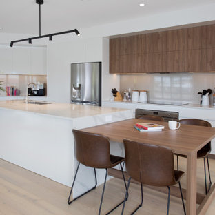Inspiration for a large contemporary galley eat-in kitchen in Gold Coast - Tweed with an undermount sink, quartz benchtops, glass sheet splashback, stainless steel appliances, light hardwood floors, with island, brown floor, white benchtop, flat-panel cabinets, white cabinets and beige splashback.
