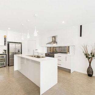 This is an example of a beach style kitchen in Gold Coast - Tweed with a double-bowl sink, flat-panel cabinets, white cabinets, window splashback, stainless steel appliances, concrete floors, with island, beige floor and white benchtop.