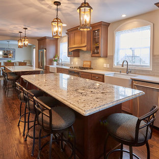 Large traditional enclosed kitchen inspiration - Inspiration for a large timeless single-wall dark wood floor and brown floor enclosed kitchen remodel in New York with a farmhouse sink, shaker cabinets, brown cabinets, gray backsplash, subway tile backsplash, stainless steel appliances, two islands and granite countertops