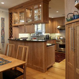 Mittelgroße Klassische Wohnküche in U-Form mit Schrankfronten im Shaker-Stil, hellbraunen Holzschränken, Küchenrückwand in Grau, Küchengeräten aus Edelstahl, hellem Holzboden, Halbinsel, beigem Boden und schwarzer Arbeitsplatte in Boston