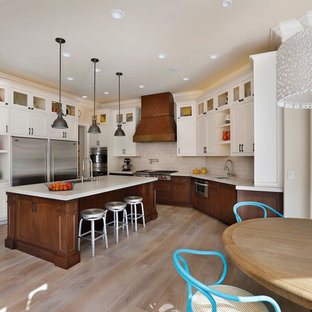 Eat-in kitchen - large transitional u-shaped beige floor and light wood floor eat-in kitchen idea in San Francisco with shaker cabinets, dark wood cabinets, white backsplash, stainless steel appliances, an undermount sink, solid surface countertops, ceramic backsplash and an island