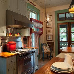 Exemple d'une cuisine bord de mer avec un électroménager en acier inoxydable, un plan de travail en bois, un placard avec porte à panneau encastré et des portes de placards vertess.