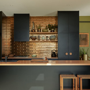 Contemporary galley kitchen in Melbourne with a drop-in sink, flat-panel cabinets, black cabinets, metallic splashback, medium hardwood floors, with island, brown floor and beige benchtop.