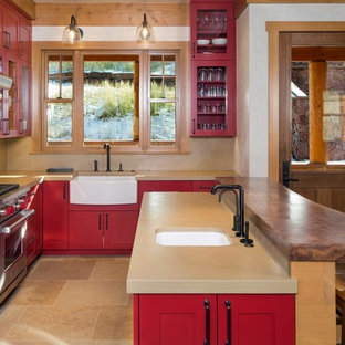 This is an example of a mid-sized country u-shaped open plan kitchen in Denver with a farmhouse sink, red cabinets, beige splashback, stone slab splashback, stainless steel appliances, a peninsula, glass-front cabinets, quartz benchtops, limestone floors and beige floor.