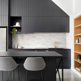 This is an example of a large contemporary l-shaped kitchen in Melbourne with an integrated sink, louvered cabinets, black cabinets, grey splashback, stainless steel appliances, with island, grey floor and black benchtop.
