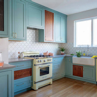 Mid-sized eclectic kitchen ideas - Example of a mid-sized eclectic l-shaped bamboo floor and brown floor kitchen design in Philadelphia with a farmhouse sink, turquoise cabinets, quartz countertops, white backsplash, ceramic backsplash, colored appliances, no island, gray countertops and shaker cabinets