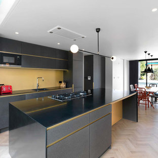 Inspiration for a contemporary kitchen/diner in London with flat-panel cabinets, black cabinets, composite countertops, yellow splashback, black appliances, an island, black worktops, a single-bowl sink, light hardwood flooring and beige floors.