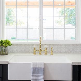 Geschlossene, Große Landhaus Küche in L-Form mit Landhausspüle, Schrankfronten im Shaker-Stil, blauen Schränken, Mineralwerkstoff-Arbeitsplatte, Küchenrückwand in Weiß, Rückwand aus Glasfliesen, Küchengeräten aus Edelstahl, braunem Holzboden, Kücheninsel, braunem Boden und weißer Arbeitsplatte in Phoenix