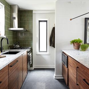 На фото: маленькая параллельная кухня-гостиная в современном стиле с врезной раковиной, плоскими фасадами, фасадами цвета дерева среднего тона, столешницей из кварцита, зеленым фартуком, фартуком из керамической плитки, техникой под мебельный фасад, полом из сланца, полуостровом, серым полом и белой столешницей с