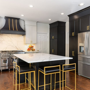 Transitional kitchen photos - Example of a transitional medium tone wood floor and brown floor kitchen design in DC Metro with shaker cabinets, black cabinets, marble countertops, multicolored backsplash, marble backsplash, stainless steel appliances, an island and multicolored countertops