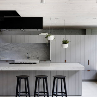 Photo of a contemporary galley open plan kitchen in Melbourne with a farmhouse sink, flat-panel cabinets, grey cabinets, grey splashback, with island and beige floor.