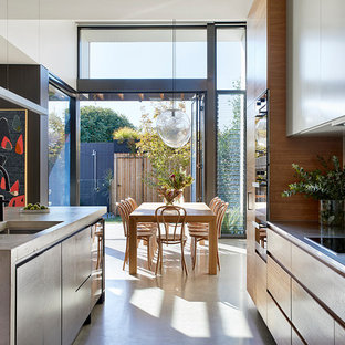 Contemporary galley open plan kitchen in Melbourne with an undermount sink, flat-panel cabinets, light wood cabinets, concrete benchtops, beige splashback, marble splashback, black appliances, concrete floors, with island, grey floor and grey benchtop.