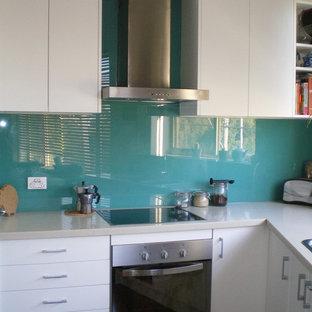 Идея дизайна: маленькая угловая кухня-гостиная в стиле модернизм с одинарной раковиной, плоскими фасадами, белыми фасадами, столешницей из кварцевого композита, зеленым фартуком, фартуком из стекла, техникой из нержавеющей стали, полом из бамбука и бежевой столешницей
