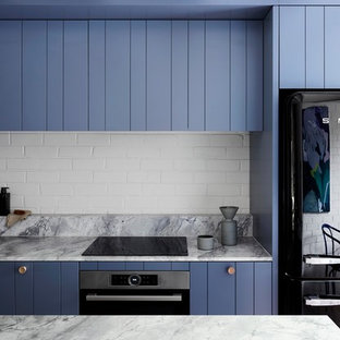 Diseño de cocina de galera, contemporánea, pequeña, abierta, con fregadero bajoencimera, puertas de armario azules, encimera de cuarcita, salpicadero blanco, salpicadero de ladrillos, electrodomésticos negros, suelo de madera en tonos medios, una isla, suelo gris, armarios con paneles lisos y encimeras grises