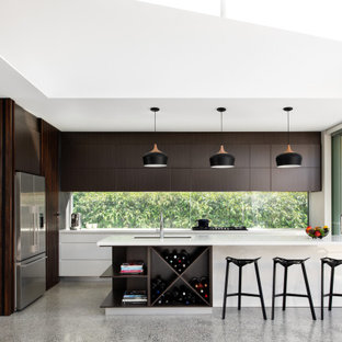 Inspiration for a contemporary l-shaped kitchen in Sydney with an undermount sink, flat-panel cabinets, dark wood cabinets, window splashback, stainless steel appliances, concrete floors, with island, grey floor and white benchtop.