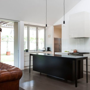 This is an example of a medium sized contemporary galley kitchen/diner in Sydney with a submerged sink, beaded cabinets, white cabinets, glass worktops, white splashback, glass sheet splashback, stainless steel appliances, concrete flooring and an island.