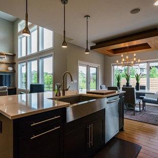 На фото: кухня-гостиная среднего размера в современном стиле с раковиной в стиле кантри, фасадами в стиле шейкер, черными фасадами, гранитной столешницей, полом из бамбука, островом, бежевым полом и бежевой столешницей