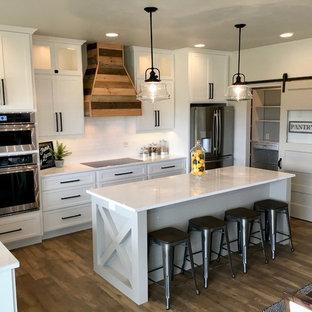 Idéer för ett mellanstort lantligt kök, med en rustik diskho, skåp i shakerstil, vita skåp, marmorbänkskiva, vitt stänkskydd, stänkskydd i tunnelbanekakel, rostfria vitvaror, vinylgolv, en köksö och brunt golv