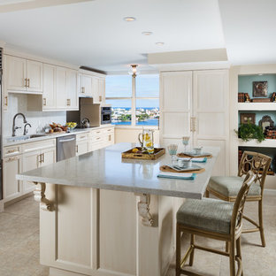 Mid-sized traditional l-shaped open plan kitchen in Miami with an undermount sink, recessed-panel cabinets, white cabinets, quartz benchtops, beige splashback, metal splashback, stainless steel appliances, ceramic floors, with island and beige floor.