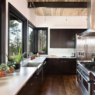Modelo de cocina en U, contemporánea, grande, con fregadero sobremueble, armarios con paneles lisos, electrodomésticos de acero inoxidable, una isla, puertas de armario negras, encimera de mármol, salpicadero blanco y suelo de madera en tonos medios