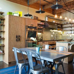 ポートランドの中サイズのインダストリアルスタイルのおしゃれなキッチン (アンダーカウンターシンク、フラットパネル扉のキャビネット、中間色木目調キャビネット、クオーツストーンカウンター、緑のキッチンパネル、ガラスタイルのキッチンパネル、シルバーの調理設備の、濃色無垢フローリング) の写真