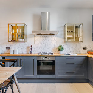 Classic l-shaped kitchen/diner in London with shaker cabinets, blue cabinets, wood worktops, white splashback, light hardwood flooring and beige floors.