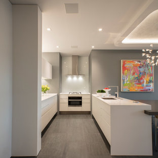 Small modern eat-in kitchen designs - Inspiration for a small modern u-shaped porcelain tile and gray floor eat-in kitchen remodel in DC Metro with an undermount sink, flat-panel cabinets, white cabinets, white backsplash, glass sheet backsplash, white appliances, an island, white countertops and quartzite countertops
