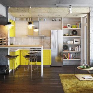 他の地域の小さいインダストリアルスタイルのおしゃれなキッチン (一体型シンク、黄色いキャビネット、黒いキッチンパネル、ガラス板のキッチンパネル、パネルと同色の調理設備、濃色無垢フローリング) の写真