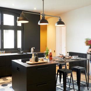 Cette image montre une cuisine nordique avec un évier 2 bacs, un placard à porte plane, des portes de placard noires, un îlot central et un sol multicolore.