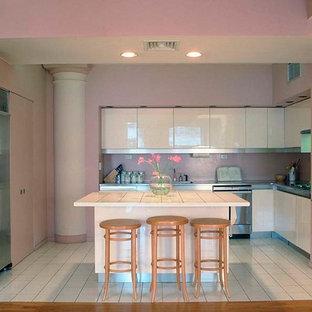 ニューヨークの大きいコンテンポラリースタイルのおしゃれなキッチン (ドロップインシンク、フラットパネル扉のキャビネット、白いキャビネット、タイルカウンター、ピンクのキッチンパネル、シルバーの調理設備の、セラミックタイルの床、ガラス板のキッチンパネル、白い床) の写真