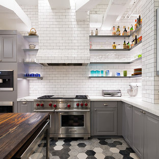 Mid-sized industrial kitchen in New York with marble benchtops, white splashback, ceramic floors, with island, a farmhouse sink, raised-panel cabinets, grey cabinets, subway tile splashback, stainless steel appliances and multi-coloured floor.