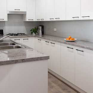 This is an example of a small modern u-shaped kitchen pantry in Melbourne with a double-bowl sink, open cabinets, white cabinets, laminate benchtops, grey splashback, glass sheet splashback, stainless steel appliances, light hardwood floors, no island and grey benchtop.