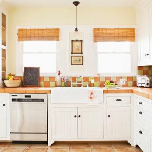 Foto på ett mellanstort shabby chic-inspirerat kök, med luckor med profilerade fronter, vita skåp, en rustik diskho, kaklad bänkskiva, stänkskydd i terrakottakakel, rostfria vitvaror, klinkergolv i terrakotta och flerfärgad stänkskydd
